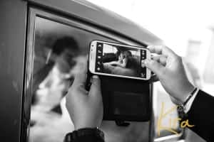 Bride and groom in the car, being photographed by guests
